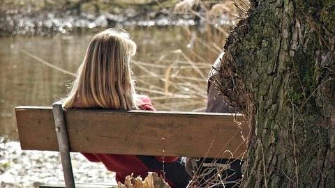 Frau sitzt alleine auf einer Parkbank