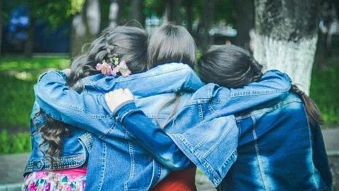 Drei Mädchen umarmen sich in inniger Freundschaft
